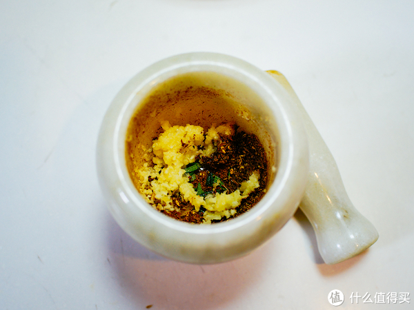 然后用壓蒜器把大蒜壓成蒜蓉,把迷迭香切碎,一起放進搗舂里,加入一小勺橄欖油和一小勺鹽,將搗舂里的香料攪拌均勻